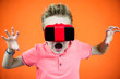 funny boy in virtual reality glasses playing smartphone on orange background