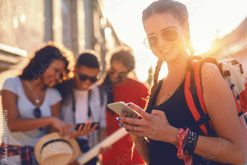 Foto  Smiling Caucasian girl with eyeglasses and backpack on backs using smart phone outdoors
