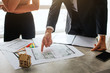 Couple buy or rent apartment together. Cut view of young woman stand near man at table. He point on apartment plan. Colorful pieces of tissues and wooden toy stand on table.