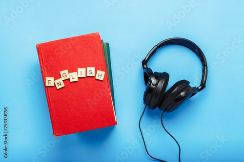 Fotografija  Book with a red cover with text English and black headphones on a blue background