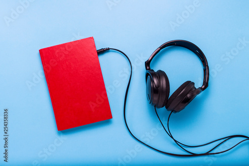 Valokuva Book with a red cover and black headphones on a blue background