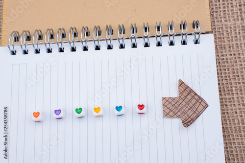 Fotografie, Obraz  Love cubes and paper arrow on a notebook