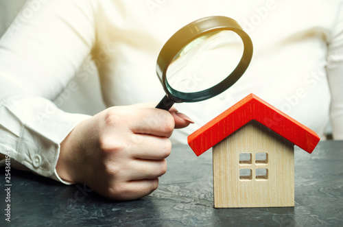 Fotografie, Obraz  A woman is holding a magnifying glass over a wooden house