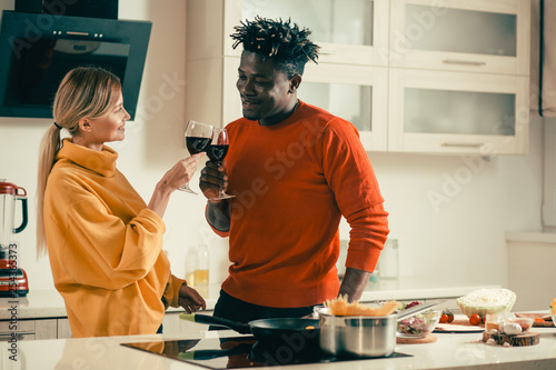 Fotografie, Obraz  Young people smiling while clanging glasses with red wine
