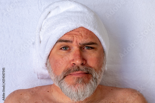 Fotografía Man prepared to receive a beauty treatment with an expression of strangeness or