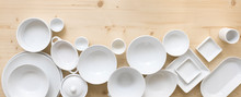 Modern, White Crockery, In Different Designs, Stands On A Light Wooden Background