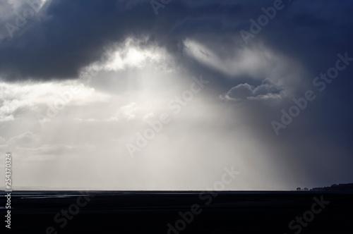 Sylwetka wioski Saint Valery sur Somme i burzliwe niebo w zatoce Somme