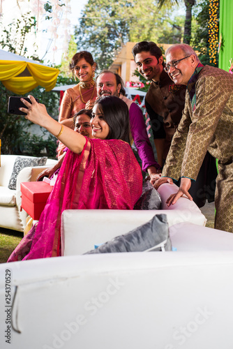 14e0596573 Indian family taking selfie picture using smartphone while wearing  traditional festival cloths on diwali/wedding ceremony and sitting on sofa  / couch