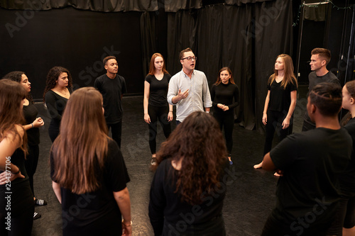 Photo Teacher With Male And Female Drama Students At Performing Arts School In Studio