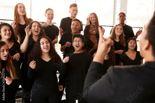 Vászonkép Male And Female Students Singing In Choir With Teacher At Performing Arts School