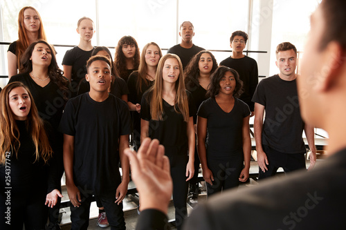 Male And Female Students Singing In Choir With Teacher At Performing Arts School - 254377742