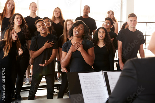 Male And Female Students Singing In Choir With Teacher At Performing Arts School - 254377782