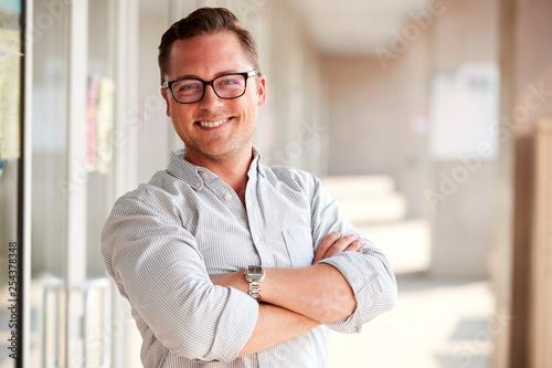 Stampa su Tela  Portrait Of Smiling Male School Teacher Standing In Corridor Of College Building