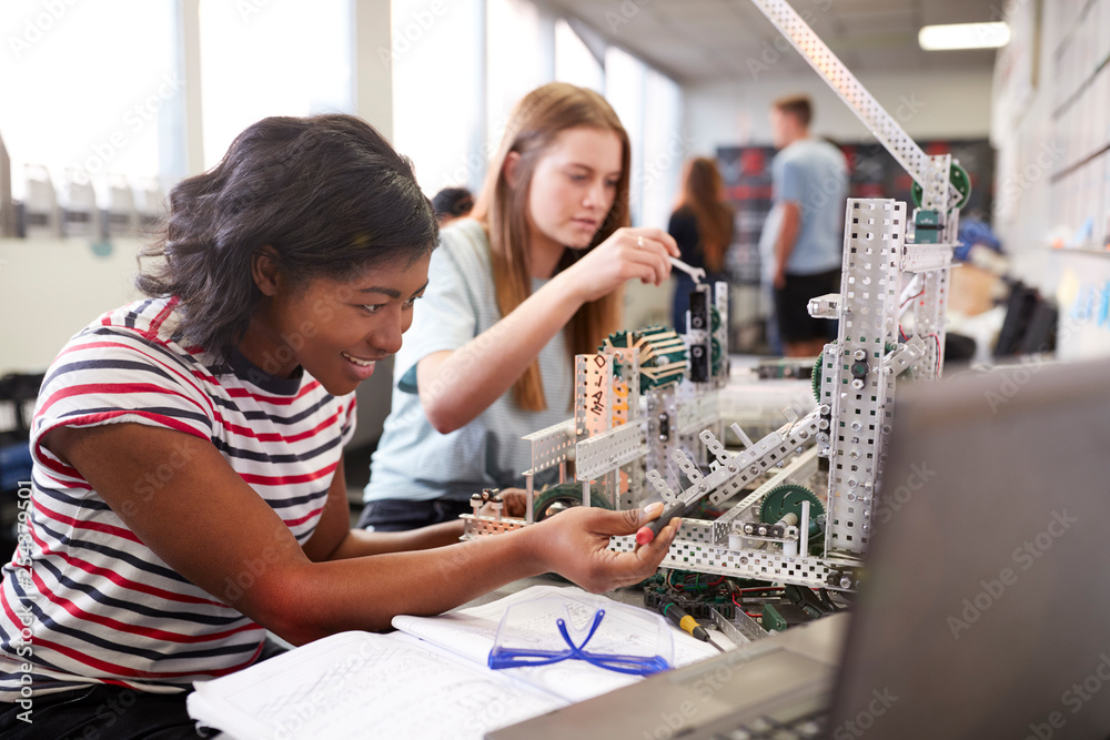 Fototapeta Two Female College Students Building Machine In Science Robotics Or Engineering Class
