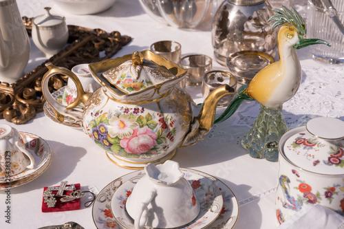 Fotografia  glass bird and vintage tea pot at street market, Cremona, Italy