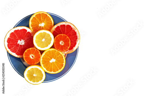 Fotografie, Obraz  halved citrus fruits on a blue plate, isolated