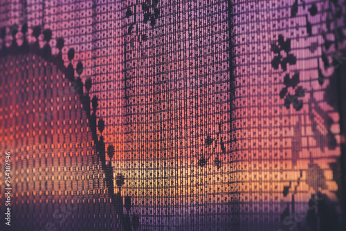Foto  Amazing romantic sunset in window behind silhouettes of tulle texture