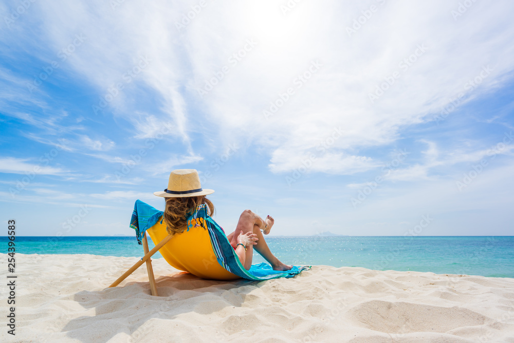 Fototapeta Woman enjoying her holidays on a transat at the tropical beach