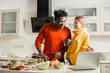 Lady pointing to the laptop while standing with boyfriend in the kitchen
