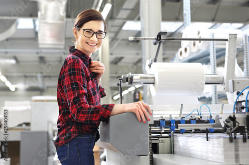 Fotografía  Praca w drukarni. Kobieta obsługuje foliarkę do druku.