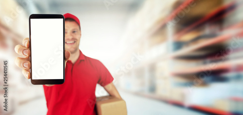 Foto  young smiling delivery service courier showing blank smart phone at warehouse