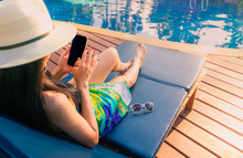 Asian Woman With Hat And Swimsuit Sit On Sunbed At Poolside And Using Smartphone On Summer Vacation By Swimming Pool. Girl With Nail Manicure And Sunglasses. Summer Vibes. Woman Relaxing On Holiday.