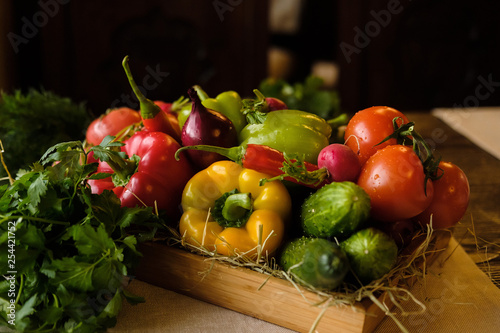 Fotografiet  Group of fresh vegetables and herbs in wooden box on wooden background