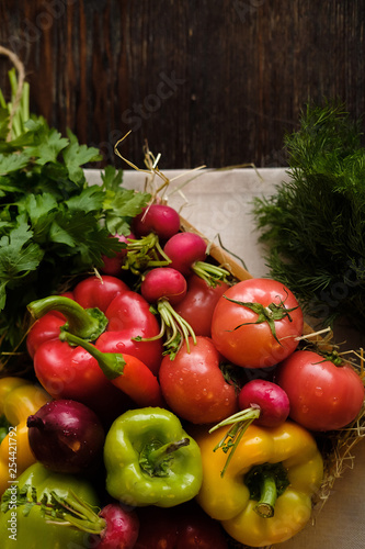 Foto  Group of fresh vegetables and herbs in wooden box on wooden background
