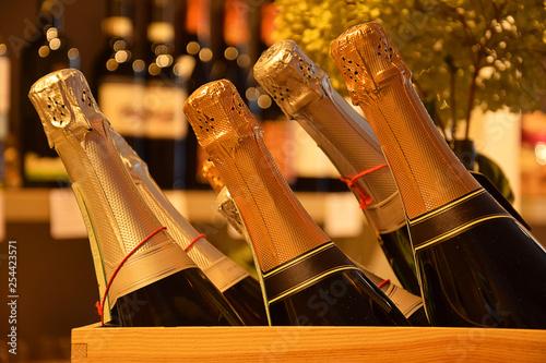 Wine bottles on wooden shelf in wine store Canvas Print