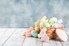 Easter Greeting Card Background With Pastel Colored Eggs And Homemade Cookies Shaped In Eggs And Bunnies Rabbits. With A Basket, Tulips, Rustic Wooden Table, Copy Space Top View Banner