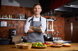 Waist up portrit of handsome chef posing standing at table with spices, copy space
