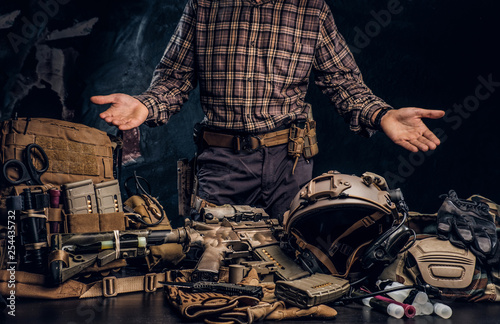 Man in a checkered shirt showing his military uniform and equipment Canvas Print
