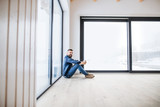 Fototapeta Łazienka - A mature man sitting on the floor in unfurnished new house, holding coffee.