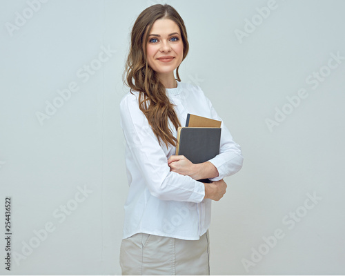 Fotografie, Obraz Smiling woman teacher wearing white shirt holding books.