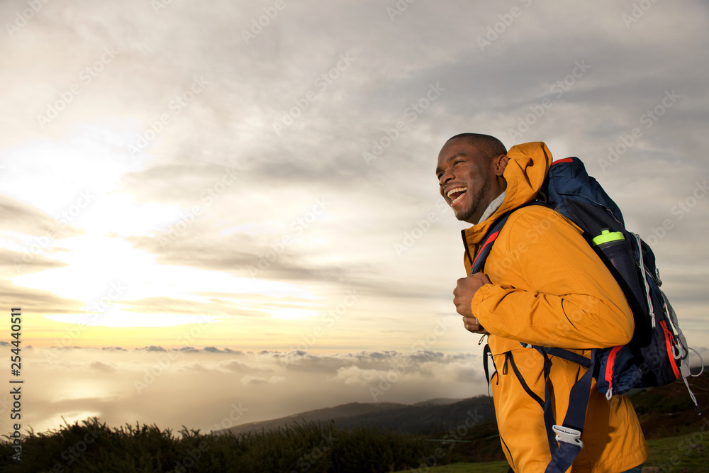 Fototapety, obrazy: happy young african american man with backpack walking in mountains