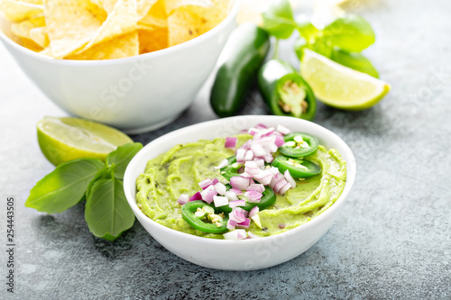 Fotografie, Obraz  Guacamole with red onion and Jalapeno pepper in a white bowl with chips