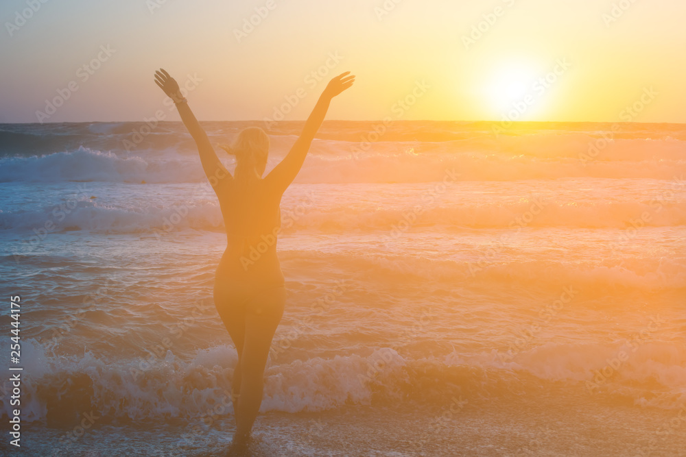Fototapety, obrazy: Girl at sunset rejoices sea on the beach