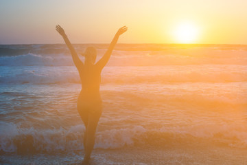 Girl at sunset rejoices sea on the beach