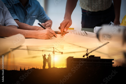 Civil Engineer Jobs, Double exposure of Project Management Team and Construction Site with tower crane background, Day and Night shift on employees job concept.