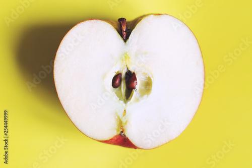 Fotografía  apple cut on a yellow background. half apple