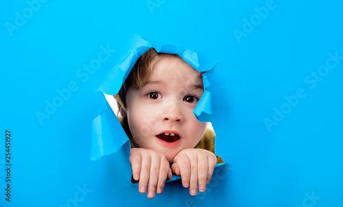 Fotografía Surprised child boy looking through hole paper