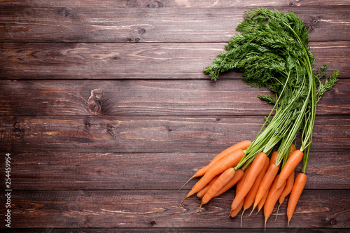Valokuva  Fresh and sweet carrot on wooden background