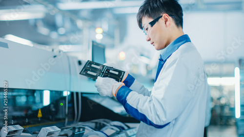 Fototapeta High-Tech Factory: Quality Control Engineer Checks Electronic Printed Circuit Board it for Damages. In the Background Assembly Line for PCB with Surface Mount Pick and Place Technology. obraz