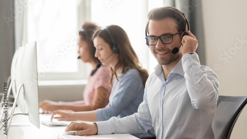 Smiling male call center operator in headset looking at camera
