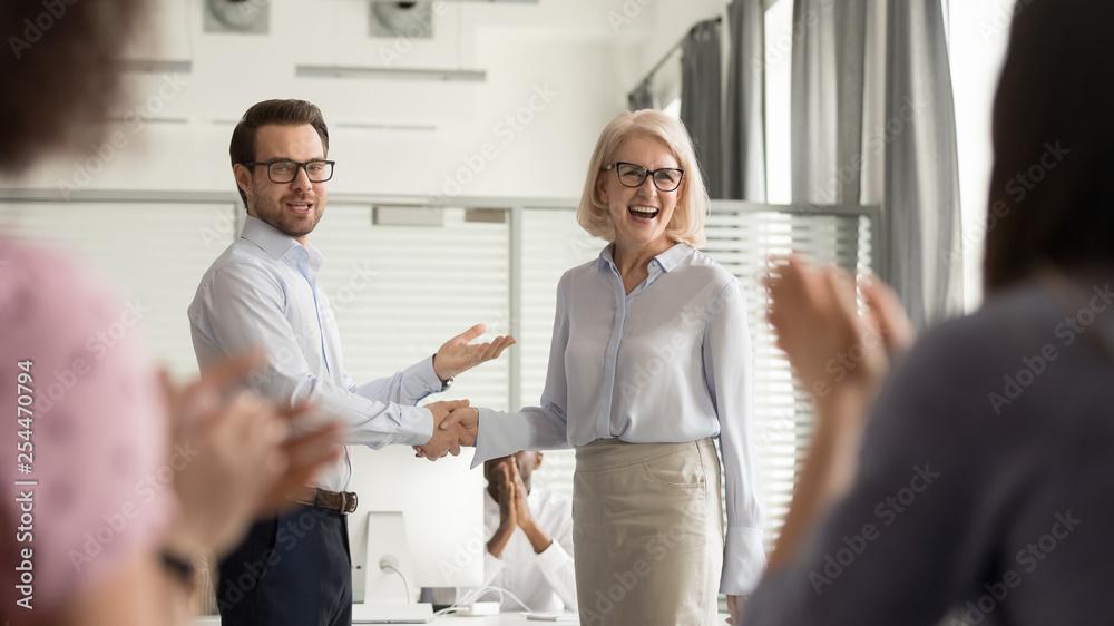Fototapeta Happy manager boss praising old employee get team appreciation