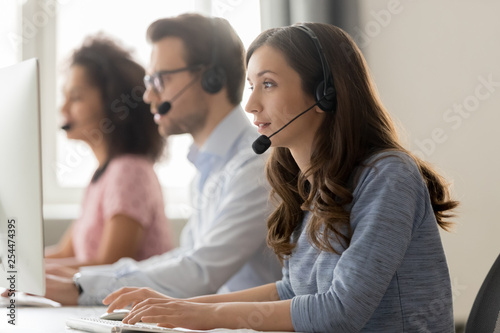 Fotografía  Young woman call center agent in headset consulting online client