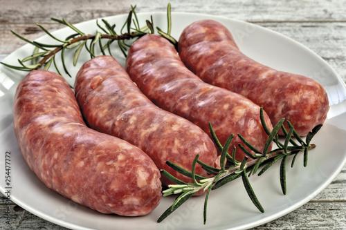 Valokuva salsicce crude con rosmarino e pomodori nel piatto da sopra