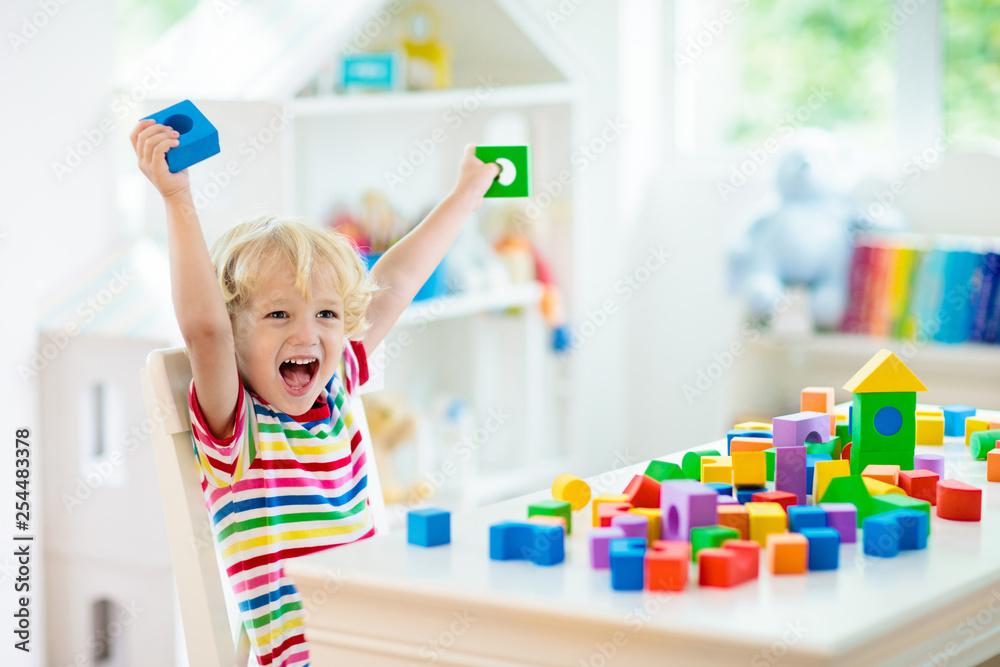 Fototapety, obrazy: Kids toys. Child building tower of toy blocks.