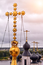 Eastern Orthodox Crosses On Gold Domes, Cupolas, Against Blue Sky With Clouds