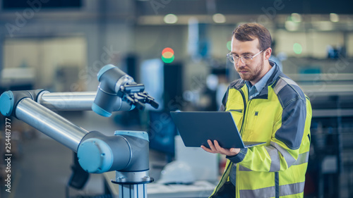 Leinwand Poster At the Factory: Automation Engineer Uses Laptop for Programming Robotic Arm